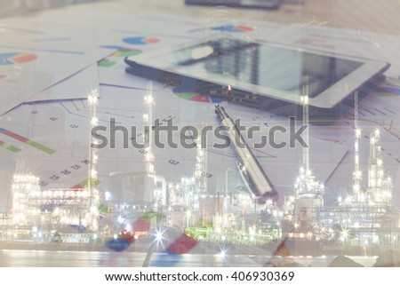 Double exposure Modern business workplace with stock market data application on blurred oil refinery background, Pen and a digital tablet, on a wood table. - stock photo