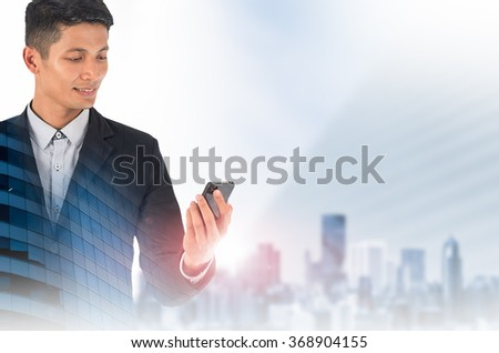 Double exposure of a businessman and a city using smartphone.