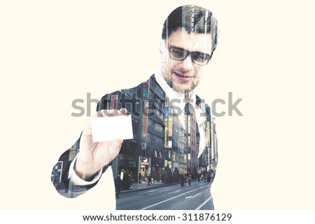 Double exposure of a businessman holding blank visiting card with city and people on the street,with clipping path  - stock photo
