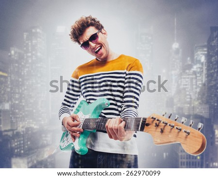 Double exposure of a city and happy man playing guitar - stock photo