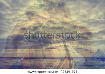 Double exposure of a man with binoculars at the ocean - stock photo