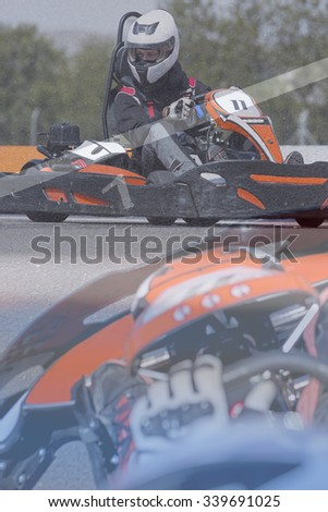 double exposure of a subjective view of a go-kart pilot on the starting line before starting a race in an outdoor go karting circuit - focus on the number one