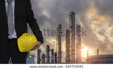 Double exposure of a young man holding a safety helmet for use safety in refinery. - stock photo