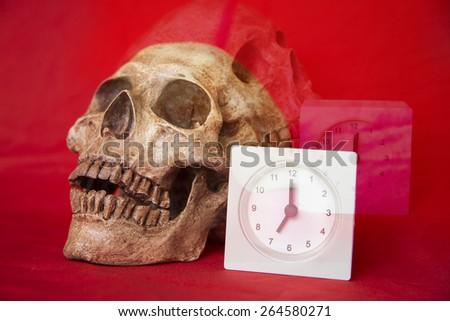 Double Exposure of alarm clock with cranium  - stock photo