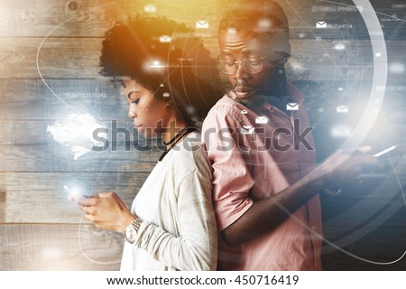 Double exposure of black girl texting her lover on cell phone while her jealous boyfriend, suspect of her betrayal, trying to read what she is typing, looking over his shoulder with curious expression - stock photo