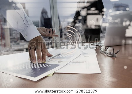 double exposure of business documents on office table with smart phone and digital tablet and stylus and two colleagues discussing data in the background - stock photo