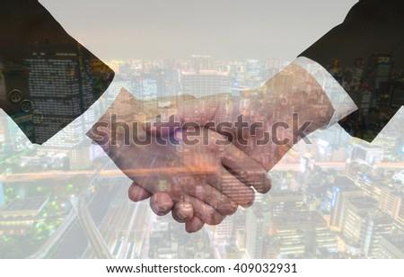 Double exposure of  Business handshake over cityscape - stock photo