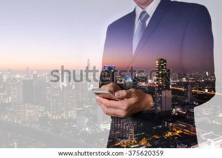Double exposure of business man hand hold and touch screen smart phone, mobile, street and night city as communication concept. - stock photo