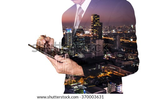 Double exposure of business man hand hold and touch screen tablet, night city and street as communication concept. - stock photo