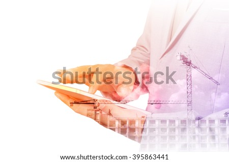 Double exposure of Business Man use Digital Tablet with Construction site and Power Crane for use as Background in Modern Real Estate development concept - stock photo