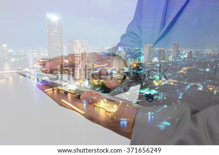 Double Exposure of Business Man using Mobile Tablet and City at Twilight as Global communication concept - stock photo