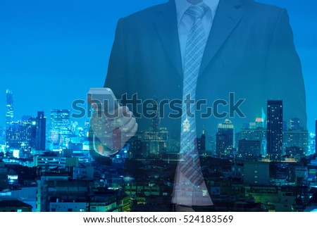 double exposure of business man using telephone or tablet on night modern city building background