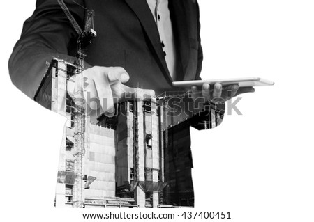 Double exposure of Business Man with Digital Tablet and Power Crane in the City as Construction Project concept.