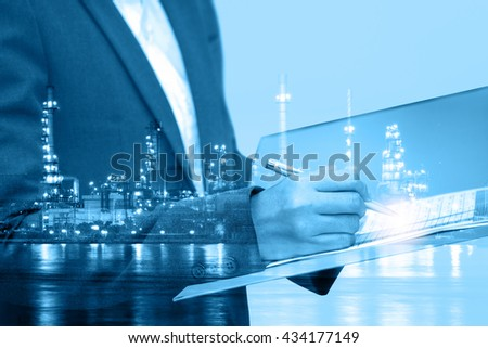 double exposure of Business woman inspect a document with blur refinery plant at night  - stock photo