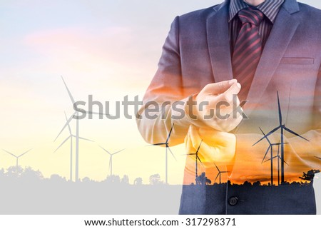 Double exposure of businessman and silhouette of wind turbine at sunset