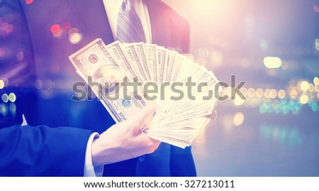 Double exposure of businessman displaying spread of cash on blurred city background  - stock photo