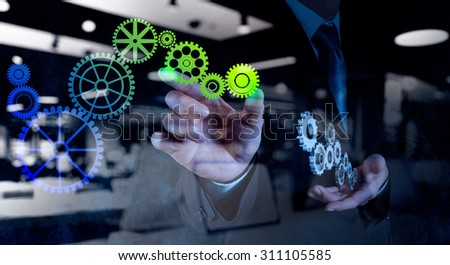 double exposure of businessman hand draws gear to success concept on touch screen computer  - stock photo