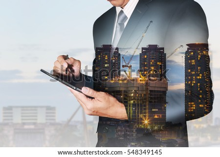 Double exposure of businessman hand hold tablet, construction crane and building in the evening, twilight as business, communication, technology and industrial concept.