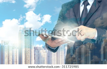 Double exposure of businessman using the tablet on cityscape background, business concept