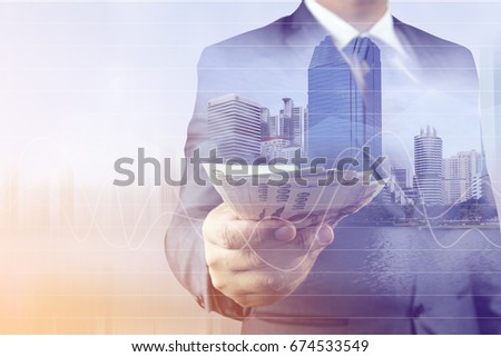 Double exposure of Businessman with money in hand with cityscape blurred building background.