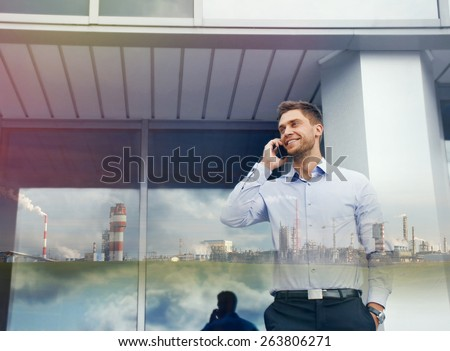 double exposure of businessman with phone device and industrial enterprise on urban building background  - stock photo