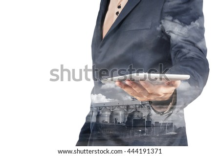 Double Exposure of Businessman with Tablet Device and Silo Plant as Technology Business Concept isolated on White Background