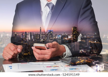Double exposure of businessman working with smartphone, cityscape, urban and street in the night as commitment, technology and communication concept.