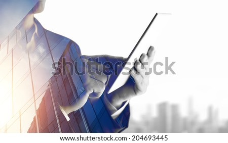 Double exposure of city and business man using digital tablet