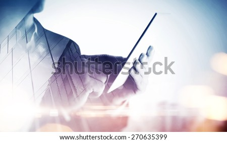 Double exposure of city and hands using tablet. With special lighting effects - stock photo