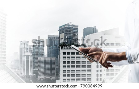 Double exposure of confident doctor in white sterile coat wirh modern cityscape view on background. Concept of modern medical industry