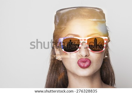 Double exposure of girl wearing sunglasses and cityscape sunset