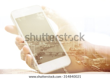 Double exposure of hand with mobile phone and bangkok thailand cityscape in the background - stock photo