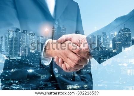 Double exposure of handshake and city night, blue tone  - stock photo