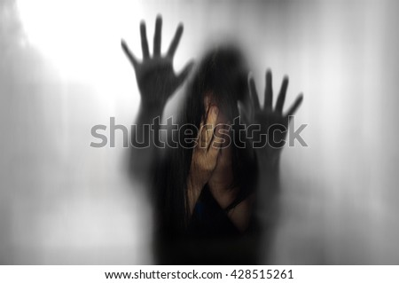 Double exposure of horror woman behind matte glass in black blurred hand and body figure and woman crying background - stock photo