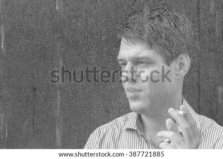 Double exposure of man smoking cigarette