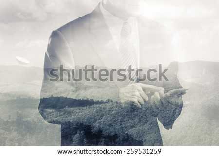 Double exposure of satellite dish on the hill and business man using smart phone - stock photo