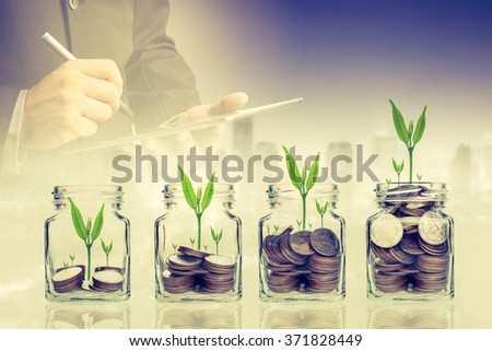 Double exposure of success businessman using digital tablet with coins with seed in clear bottle,Business investment growth concept,saving concept on city landscape background - stock photo