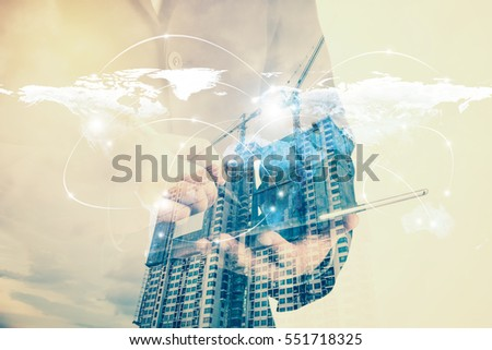Double exposure of success businessman using digital tablet with Construction site with crane and building.connection symbols communication lines. Elements of this image furnished by NASA.