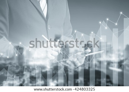 Double exposure of success businessman using digital tablet with financial graph on blurred city landscape background, Business Trading concept - stock photo