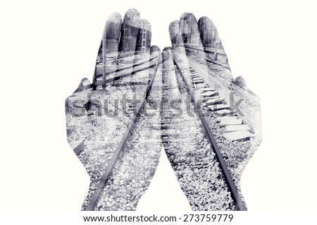 double exposure of the palms of a man put together and a railway, in black and white - stock photo