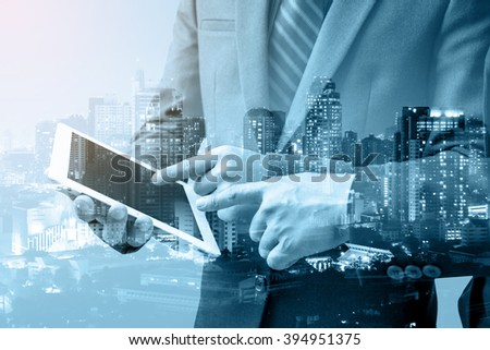 double exposure of two businessmen using tablet at meeting with blur city night, Blue tone  - stock photo