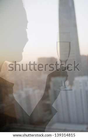 Double exposure of woman toasting with champagne flute over cityscape