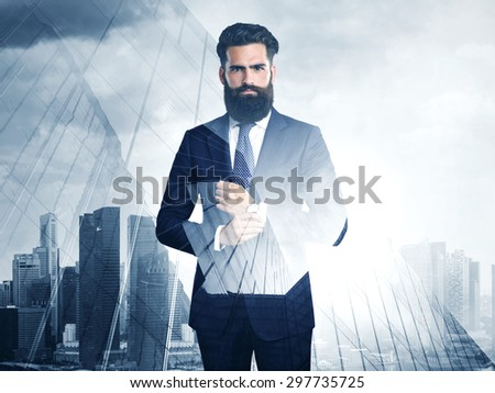 Double exposure of young bearded businessman and city on the background - stock photo