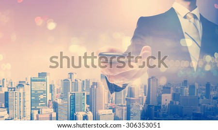 Double exposure of young businessman holding a smartphone on city background - stock photo
