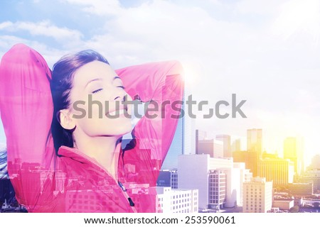 Double exposure of young joyful beautiful woman over cityscape. City woman happy standing excited elated arms raised in joy taking deep breath celebrating freedom. New York city skyline background