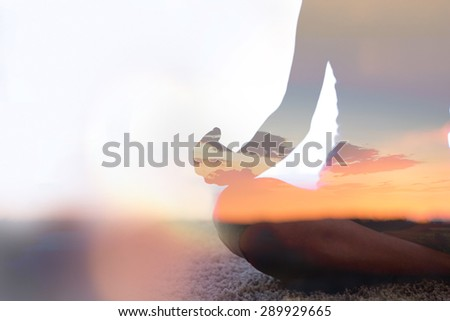 Double exposure of young woman  silhouette practicing yoga - stock photo