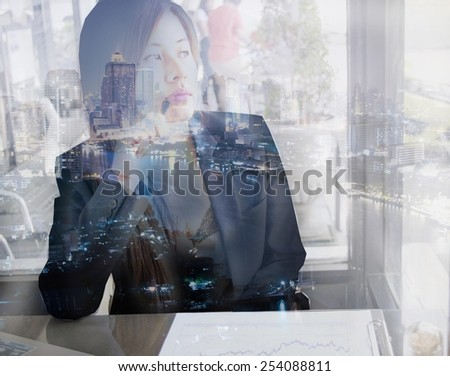 Double exposure portrait of an Asian working woman thinking about big city while she's working at cafe. - stock photo