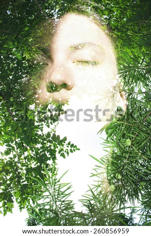 Double exposure portrait of attractive lady combined with photograph of tree - stock photo
