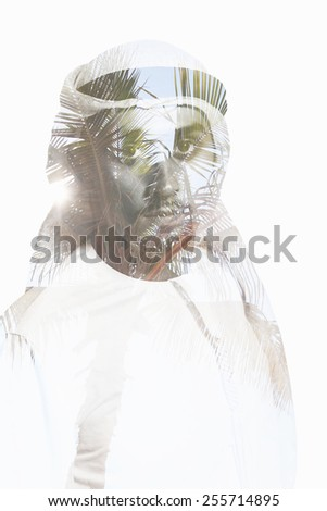 Double exposure portrait of attractive man combined with photograph of palm tree - stock photo
