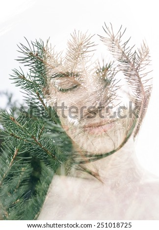 Double exposure portrait of attractive woman combined with photograph of fir branches - stock photo